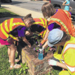 Girl Scouts clean up, plant flowers downtown